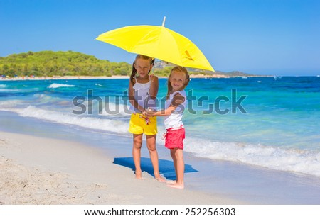 Little girls with big yellow umbrella during tropical beach vacation