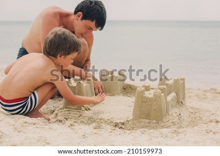 little kid and his father building sandcastle