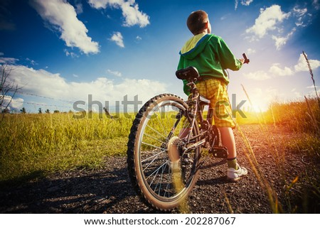 little kid with his bicycle in the field