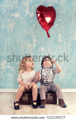 Little kids holding and picking up heart balloon. Valentine's Day and love concept