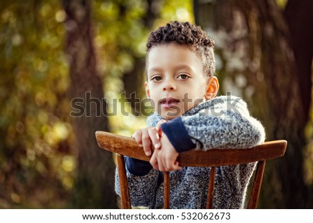 Little mixed race boy sitting on a chair