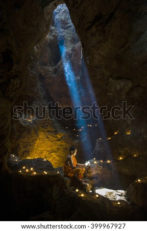 Little monk is praying and reading book in the cave