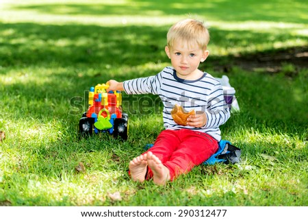 Little preschool boy playing with big toy car and having fun, outdoors.