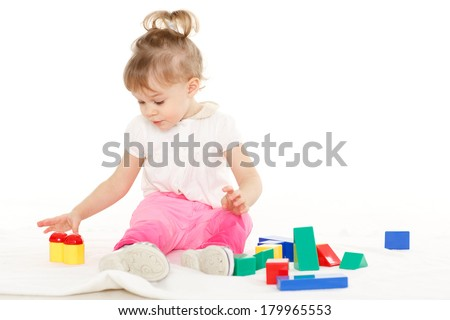 Little pretty girl plays with children blocks set on a white background. Learning toys and early development.