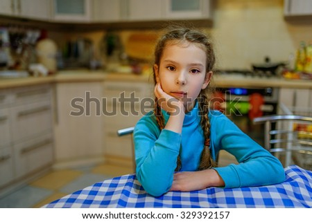 Little pretty thoughtful girl on the background of the kitchen.