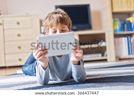 Little schoolboy having fun with his tablet in the living room