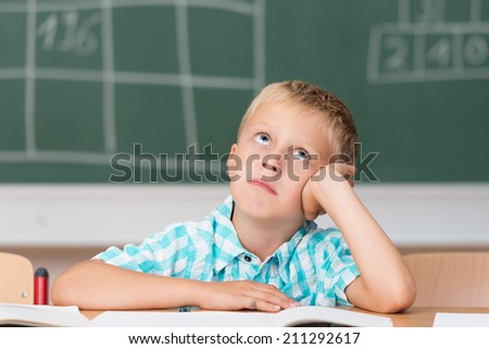 Little schoolboy without an answer staring up into the air hoping for inspiration as he sits at his desk in front of the blackboard