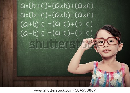little schoolgirl with green chalkboard with math formulas