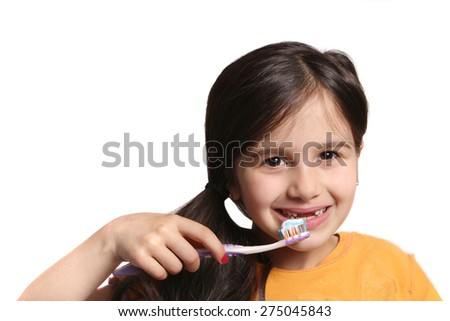Little seven year old girl shows big smile showing missing top front teeth and holding a toothbrush with toothpaste on a white background