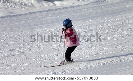 Little skier on ski slope at sun winter morning