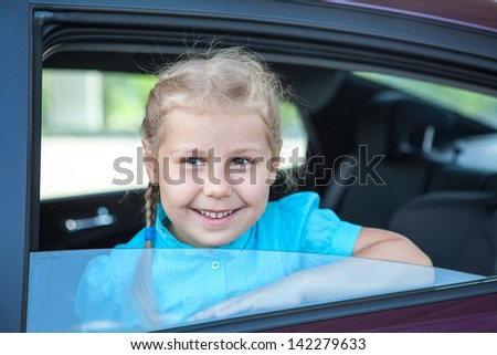 Little smiling Caucasian girl inside of back seat of car