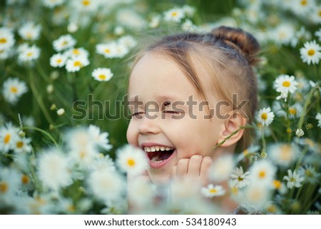 Little smiling girl blonde woman with ladybug on her face in the summer among daisies. Nature and children.