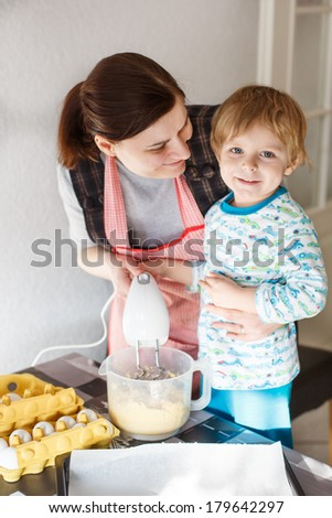 Little toddler boy and his mother having fun with baking at home kitchen