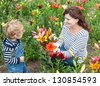 Little toddler boy and young woman on lily field in summer, Germany - stock photo