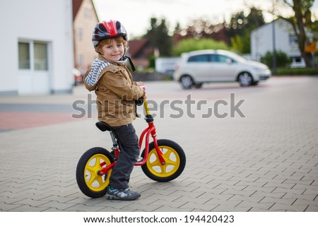 Little toddler boy learning to ride on his first bike  in the city