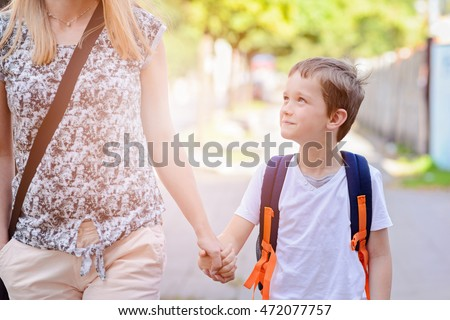 Little 7 years old boy going to school with his mother