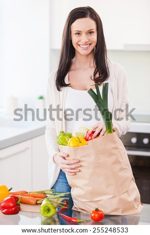 Living a healthy life. Beautiful young woman unpacking shopping bag full of fresh vegetables and smiling while standing in the kitchen