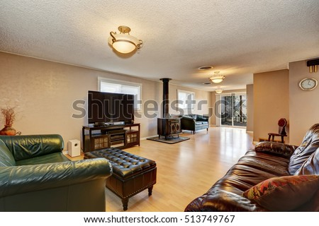 Living Room With Antique Fireplace Leather Sofas And Ottoman Light Brown Hardwood Floor