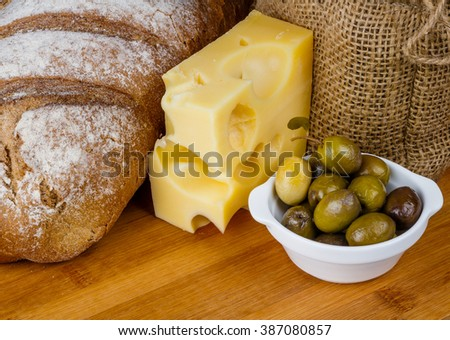 Loaf of bread, piece of cheese, and olives in a white bowl