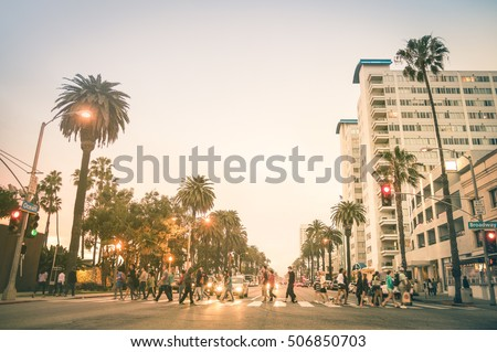 Locals and tourists walking on zebra crossing on Ocean Ave in Santa Monica after sunset - Crowded streets of Los Angeles and California state - Warm desat twilight color tones with blurred people