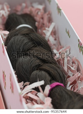 Lock of Hair Braided and placed in a pink box ready to be donated for a cancer survivor's wig. Selective focus.