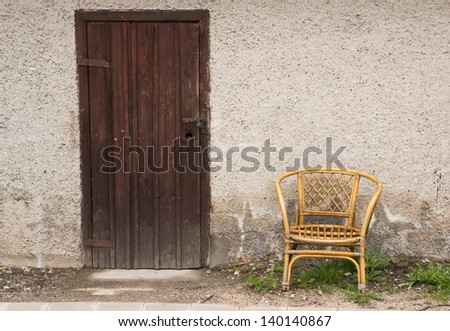 Locked wooden door and a chair against the wall
