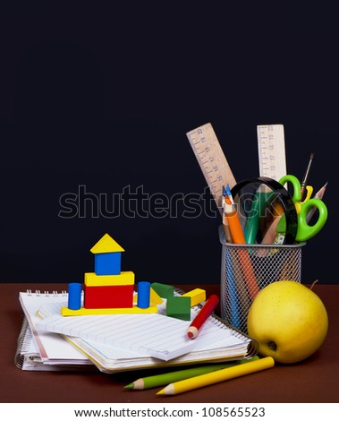 lodge from cubes, pencils, empty notebooks against a blackboard