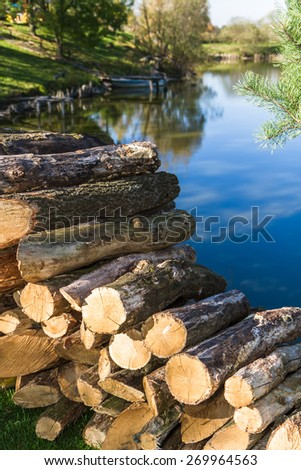 Logs of wood stacked. Lake background.