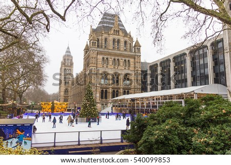 LONDON, ENGLAND - December 17, 2016: People in the Christmas skating rink by the Natural History Museum. The famous museum is one of the various city places with holiday decoration and attractions.