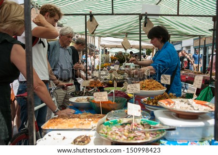 LONDON, ENGLAND - JULY 14: People deciding what to buy from a market stall of prepared food at the Columbia Road Flower Market in Lindon, UK on July 14, 2013.
