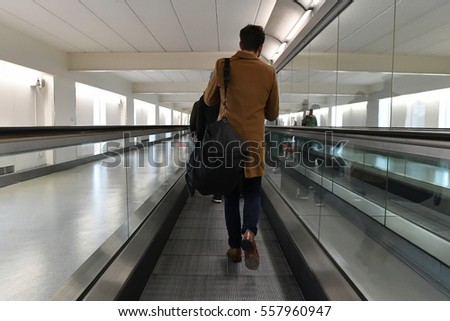 London Heathrow Airport, UK - December 2, 2016: A man walks on a moving walkway through Heathrow Airport.