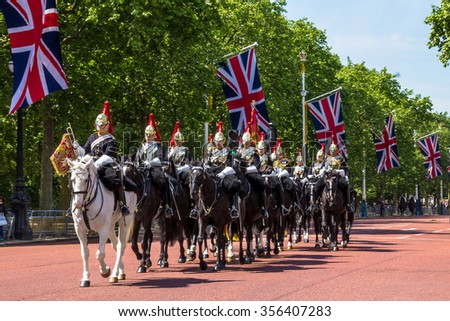 LONDON, UK - JUNE 4, 2015:  Household Cavalry walk along The Mall in London, England, towards Buckingham Palace.  The parade of the Horse Guards is very popular with visitors.