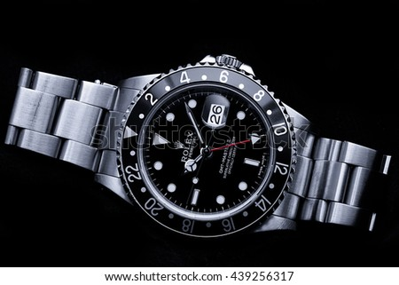 London, UK - 26 March 2016: A black bezel Rolex GMT Master II reference 16710 mechanical watch.  Known as the black GMT. The watch is on a Rolex Oyster bracelet and resting on a black background.