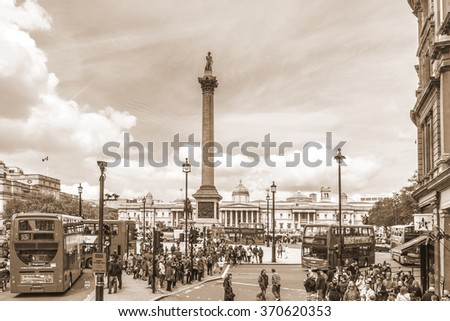 LONDON, UK - MAY 25, 2013: Tourists visit Trafalgar Square in London. Trafalgar Square - the largest square in London, is often considered the heart of London. Vintage, sepia.