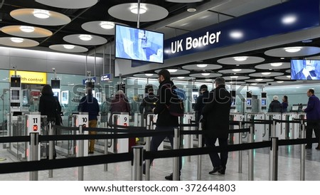 LONDON, UK - NOV 18, 2015: Air travelers queue at border passport control entrance gates at Heathrow Airport. The British aviation hub is the busiest in the European Union by passenger traffic.