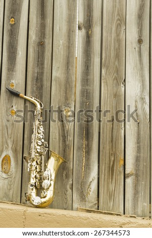 Lone old saxophone leans against wooden fence outside jazz club