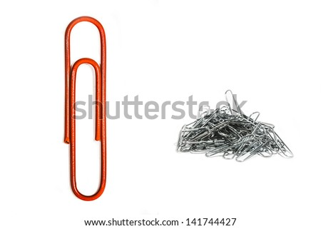 Lone red paper clip uniquely presented amongst others