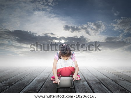 lonely cute girl using digital tablet on wooden floor under cloudy blue sky