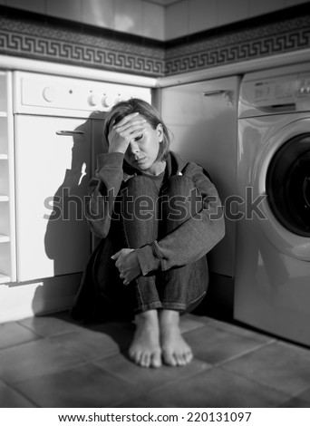 lonely depressed and sick woman sitting alone on kitchen floor in stress , depression and sadness feeling miserable in barefoot looking desperate in black and white vertical composition