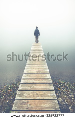 lonely man on a wooden pier