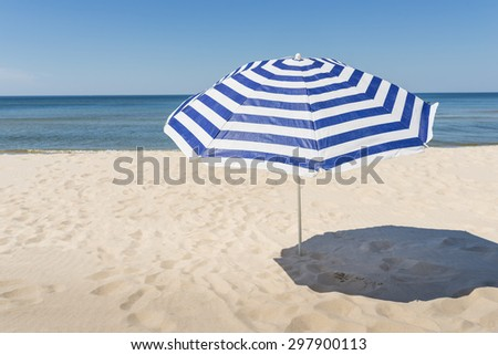 Lonely white and blue strip umbrella on the beach.