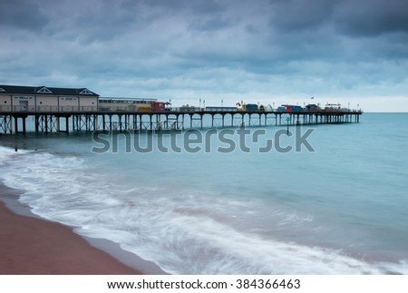 Long exposure landscape image, showing smooth sea water around Teignmouth Grand pier, under a stormy sky. Taken in the Uk.