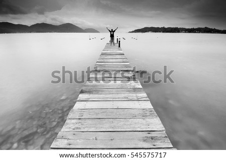 long exposure of man open arms to express victory and freedom at wooden jetty at sea facing island with cloud and sky at twilight in black and white .