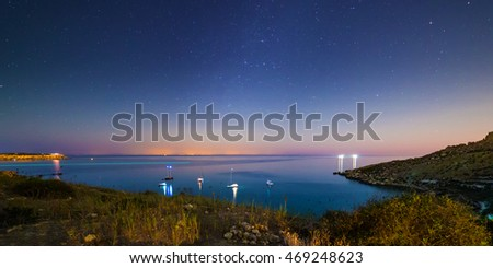 Long exposure of Mgiebah Bay in Malta on a clear summer night.  Street lights from Sicily can be clearly seen in the background on the horizon. Astronomical long exposure image, may contain some noise