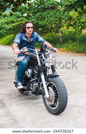 Long-haired brunette guy in sunglasses jeans and a denim shirt posing on a black ?ustom motorcycle