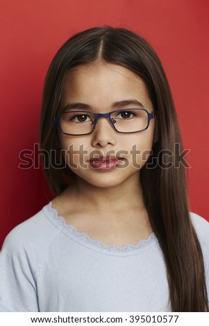 Long haired girl in spectacles against red background