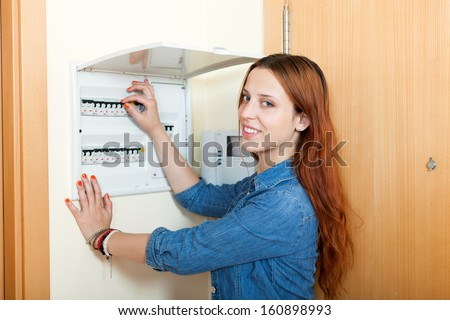 Long-haired woman turning off the light-switch at power control panel in home