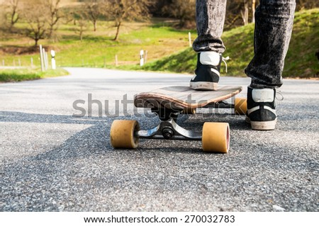 Longboard and feet of young boy in sneakers on a road