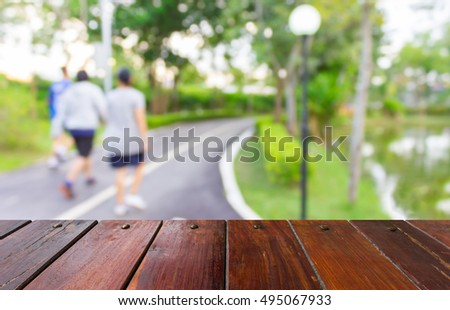 Look out from the table, blur image of people exercise in the park as background.