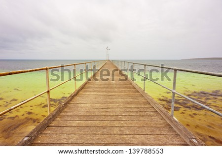Looking along a long pier into the distant horizon.